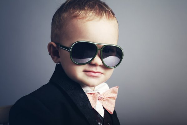 Young boy dressed as a gentleman with sunglasses