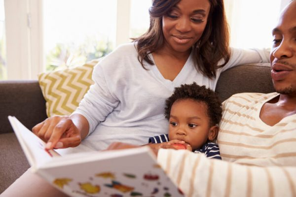 Parents And Son Reading Book On Sofa At Home Together