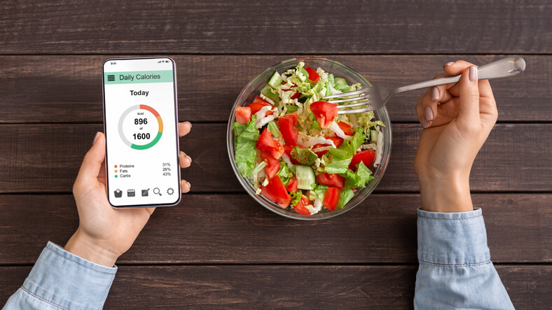 Woman eating vegetable salad and counting calories on mobile application