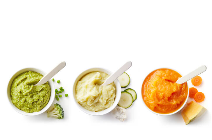 Three bowls of baby puree isolated on white