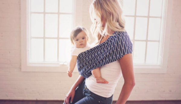 a mom carrying her baby in a sling