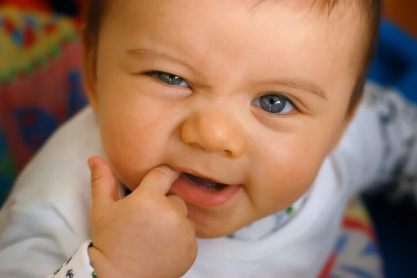 A baby in crib and pajamas teething on finger