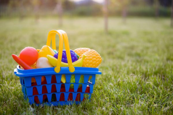 Bright plastic colorful basket with toy fruits and vegetables outdoors on sunny summer day