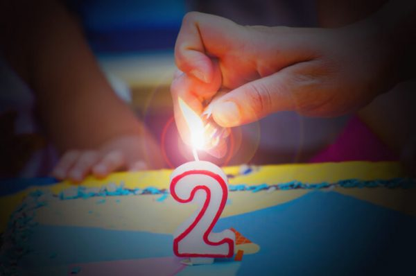 Hand with a lighter about to fire a two years birthday candle