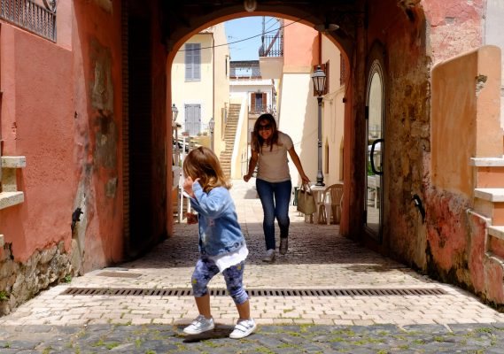 Little girl plays with her mother in a small and characteristic Italian village